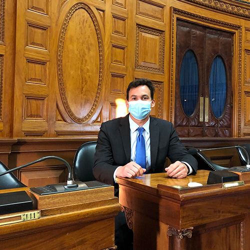 Dan Sena sitting at State House desk with mask