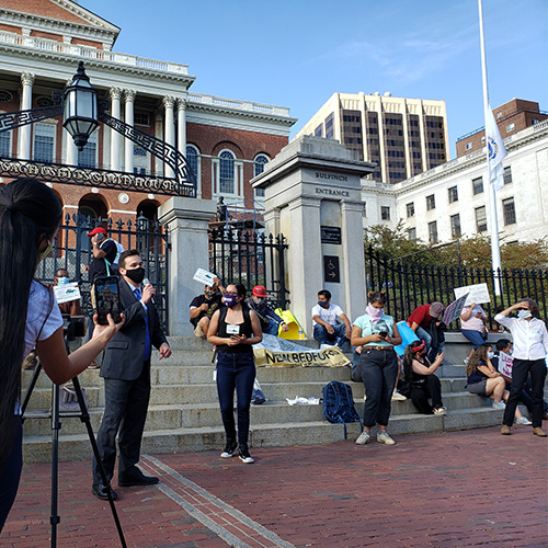 Dan Sena speaks in front of the State House Steps at masked and socially distant event